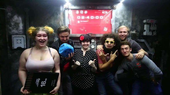 Photo of clueQuest staff in front of an escape room