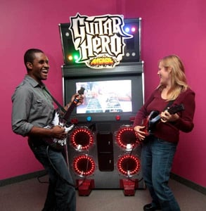 Photo of a couple playing Guitar Hero