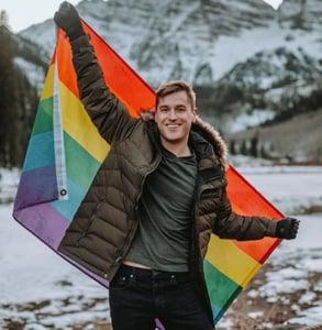 Photo of Mikah with a rainbow flag