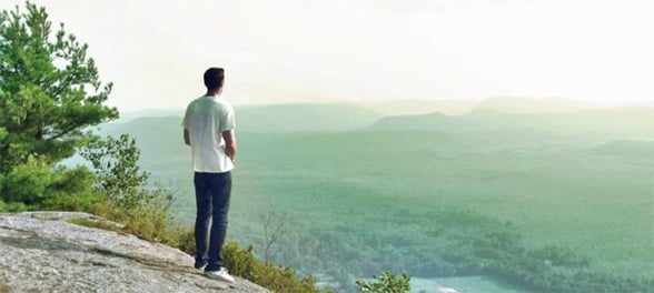 Photo of a man looking at mountains